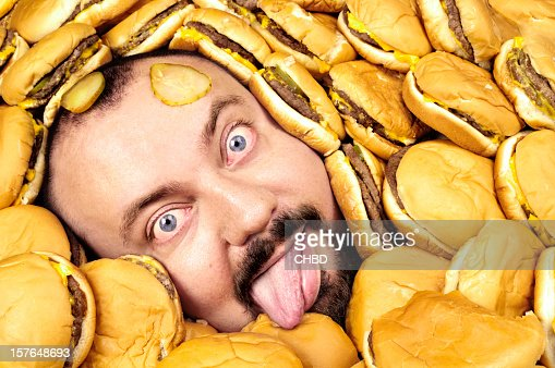 Hungry man half buried in a pile of hamburgers