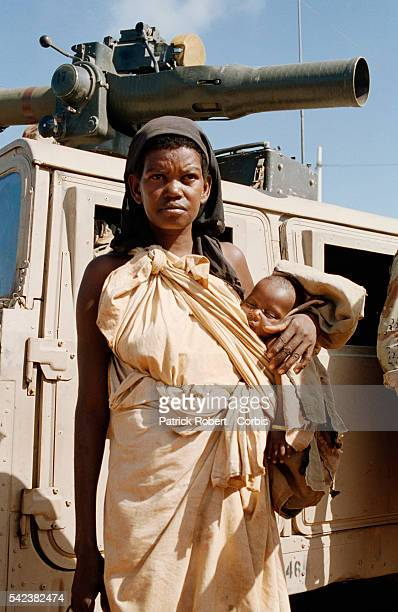 A hungry mother and her infant child stand before an American military vehicle during Operation Restore Hope Operation Restore Hope is the American...