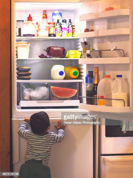 Hungry Toddler Standing By Fridge.