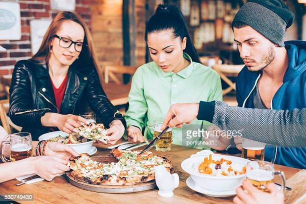 Hungry young people dining and having fun in restaurant