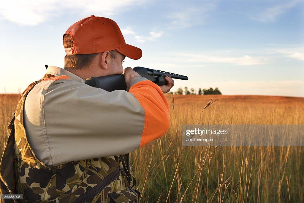 Hunter aiming rifle in field