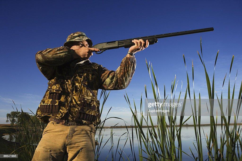 Hunter aiming rifle near reeds