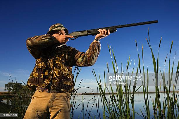 Hunter aiming rifle near reeds