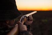 Hunter aiming shotgun at flying objects  in dusk