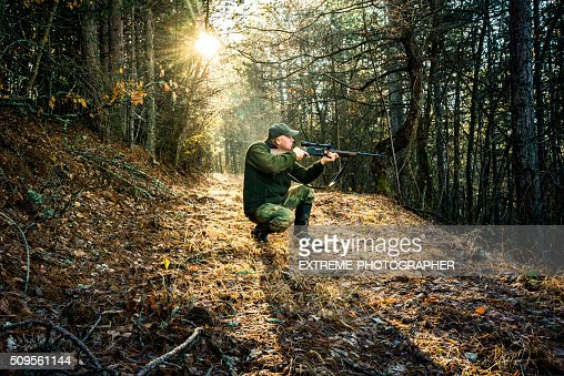 Hunter aiming with rifle in the forest