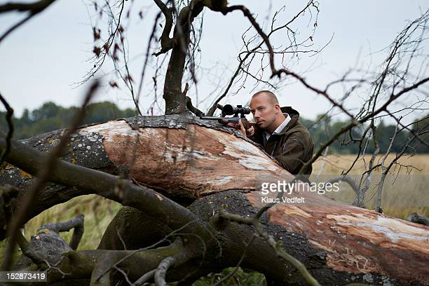 Hunter aiming with rifle resting on dead tree