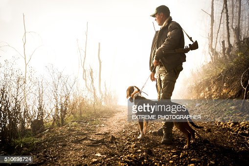 Hunter and his dog in the forest