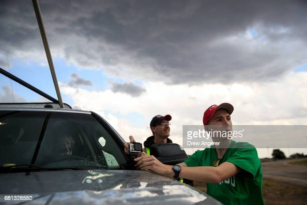 Hunter Anderson intern at Center for Severe Weather Research prepares a GoPro camera while monitoring a thunderstorm during a tornado research...