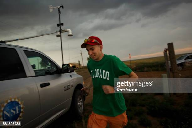 Hunter Anderson intern with the Center For Severe Weather Research hustles back to the tornado scout vehicle while a supercell thunderstorm develops...