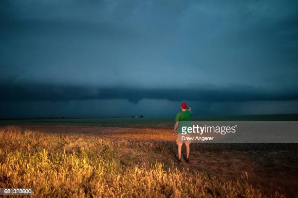 Hunter Anderson intern with the Center For Severe Weather Research gets out of the tornado scout vehicle to observe a supercell thunderstorm as it...