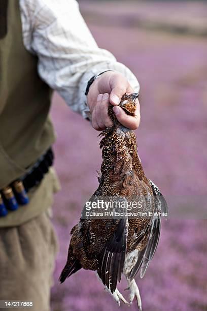 Hunter carrying dead bird