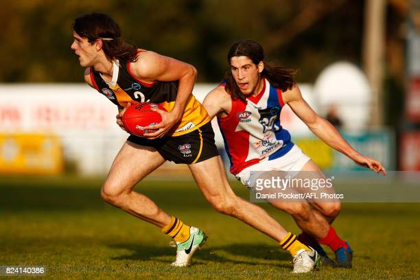 Hunter Clark of the Stingrays breaks away from Kim Drew of the Power during the round 14 TAC Cup match between Dandenong and Gippsland at Frankston...