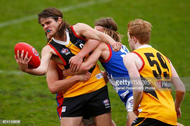 Hunter Clark of the Stingrays handpasses the ball under pressure during the round 14 TAC Cup match between Dandenong and Gippsland at Frankston Oval...
