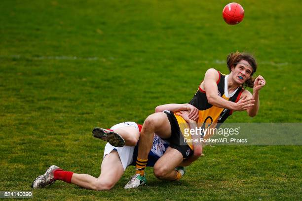 Hunter Clark of the Stingrays handpasses the ball whilst being tackled by Bailey Beck of the Power during the round 14 TAC Cup match between...