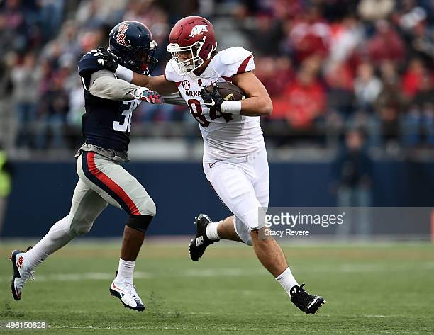 Hunter Henry of the Arkansas Razorbacks is pursued by Zedrick Woods of the Mississippi Rebels during the second quarter of a game at VaughtHemingway...