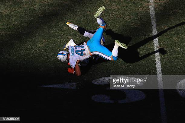 Hunter Henry of the San Diego Chargers is tackled by Kiko Alonso of the Miami Dolphins during the second half of a game at Qualcomm Stadium on...