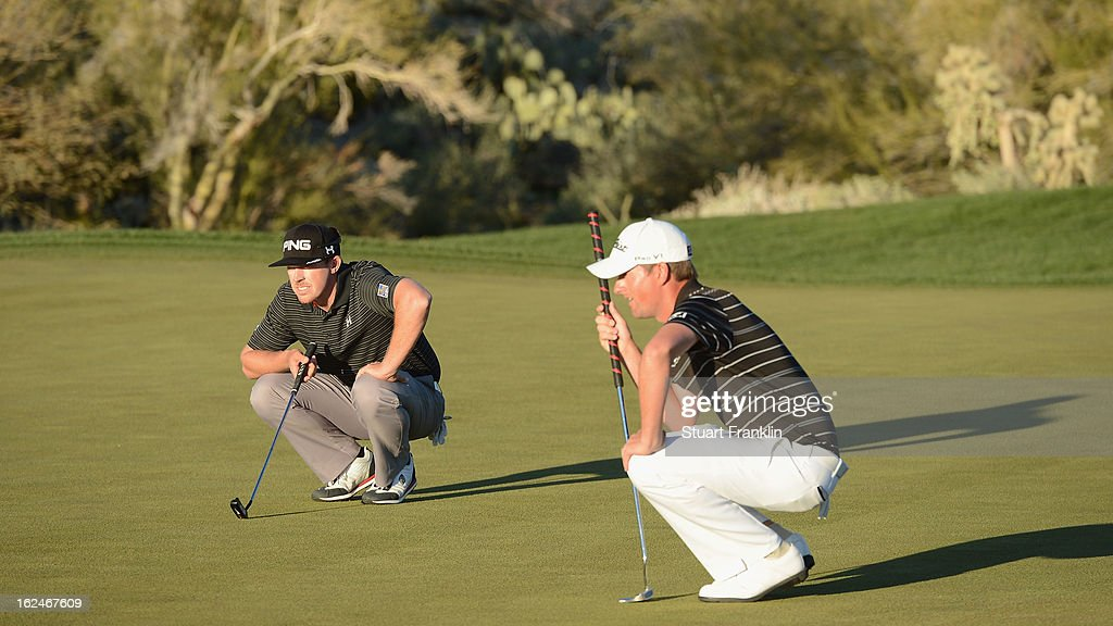 Hunter Mahan and Webb Simpson after Simpson line up their putts on the 18 holes during the quarterfinal round of the World Golf Championships - Accenture Match Play at the Golf Club at Dove Mountain on February 23, 2013 in Marana, Arizona.