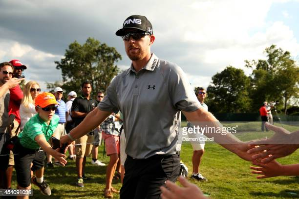 Hunter Mahan greets fans as he walks from the 13th green to 14th tee during the final round of The Barclays at The Ridgewood Country Club on August...