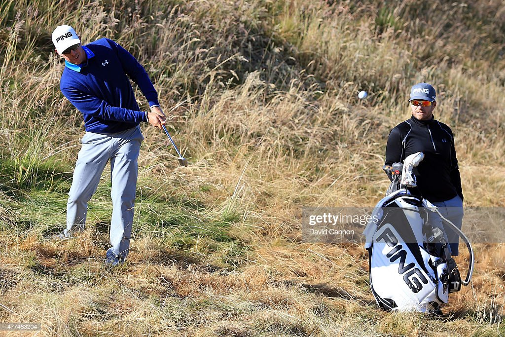 Hunter Mahan of the United States chips to a green as caddie John Wood looks on during a practice round prior to the start of the 115th U.S. Open Championship at Chambers Bay on June 17, 2015 in University Place, Washington.