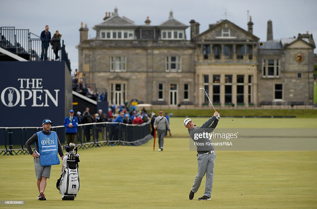 Hunter Mahan of the United States hits an approach shot on the first hole as caddie John Wood looks on ahead of the 144th Open Championship at The Old Course on July 14, 2015 in St Andrews, Scotland.