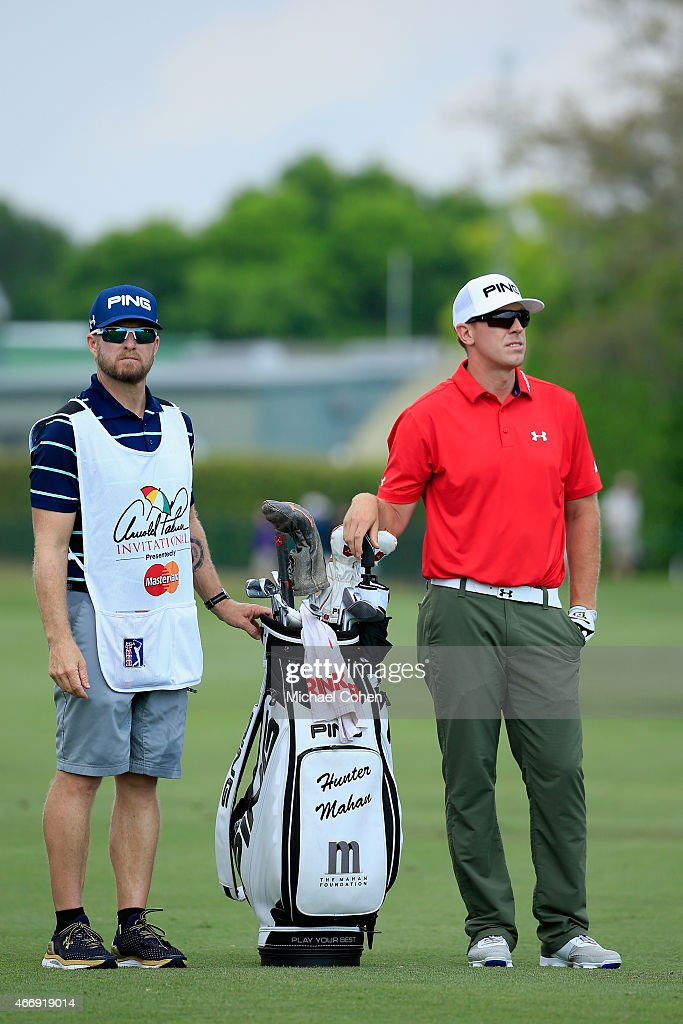 Hunter Mahan of the United States waits to hit his second shot on the ninth hole alongside caddie John Wood during the first round of the Arnold...
