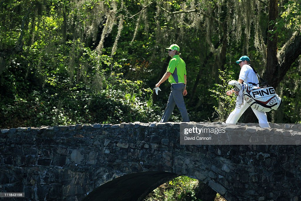 Hunter Mahan walks over the Nelson bridge back to 13 tee with his caddie John Wood during the first round of the 2011 Masters Tournament at Augusta...