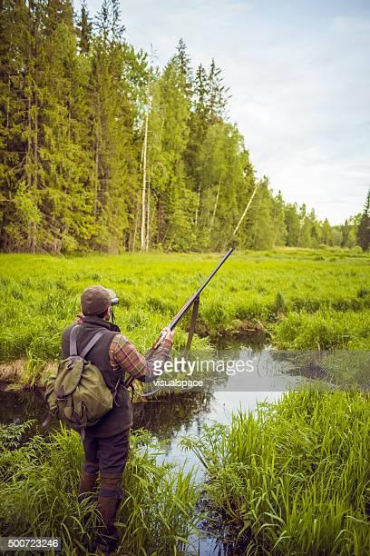 Hunter Man Looking For Prey in Open Swamp Scenery