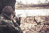 Man with gun prepared to shot  in rural field during hunting season
