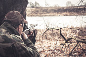Man with gun prepared to shot  in rural field during hunting season