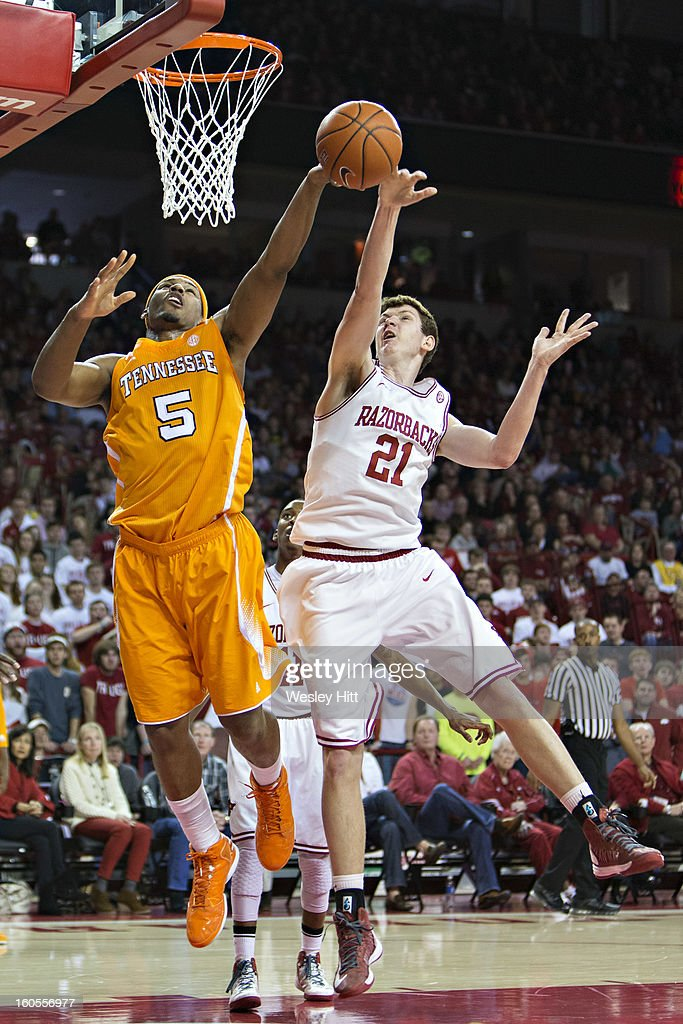 Hunter Mickelson #21 of the Arkansas Razorbacks blocks the shot of Jarnell Stokes #5 of the Tennessee Volunteers at Bud Walton Arena on February 2, 2013 in Fayetteville, Arkansas. The Razorbacks defeated the Volunteers 73-60.