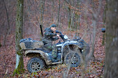 Young hunter on a quad bike searching for game in the forest