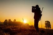 Hunter on the morning hunt. Hunter shoots at the wild animal