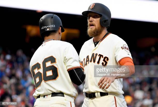 Hunter Pence and Gorkys Hernandez of the San Francisco Giants celebrate after scoring on a threerun home run by Buster Posey against the Chicago Cubs...