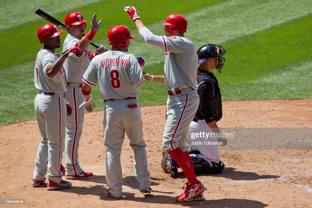 <a gi-track='captionPersonalityLinkClicked' href=/galleries/search?phrase=Hunter+Pence&family=editorial&specificpeople=757341 ng-click='$event.stopPropagation()'>Hunter Pence</a> #3 of the Philadelphia Phillies celebrates at home plate after hitting a two-run home run with <a gi-track='captionPersonalityLinkClicked' href=/galleries/search?phrase=Shane+Victorino&family=editorial&specificpeople=576251 ng-click='$event.stopPropagation()'>Shane Victorino</a> #8, <a gi-track='captionPersonalityLinkClicked' href=/galleries/search?phrase=Jimmy+Rollins&family=editorial&specificpeople=204478 ng-click='$event.stopPropagation()'>Jimmy Rollins</a> #11 and Carlos Ruiz #51 as catcher <a gi-track='captionPersonalityLinkClicked' href=/galleries/search?phrase=Ramon+Hernandez&family=editorial&specificpeople=179461 ng-click='$event.stopPropagation()'>Ramon Hernandez</a> #55 of the Colorado Rockies looks on during the fifth inning at Coors Field on July 15, 2012 in Denver, Colorado. The Phillies defeated the Rockies 5-1.