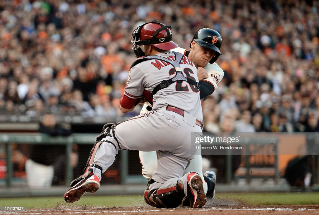 Hunter Pence of the San Francisco Giants attempting to score on a ground ball to third base is tagged out colliding with catcher Miguel Montero of...