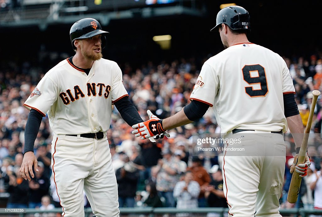 Hunter Pence #8 of the San Francisco Giants is congratulated by Brandon Belt #9 after Pence hit a solo home run in the seventh inning against the Miami Marlins at AT&T Park on June 23, 2013 in San Francisco, California.