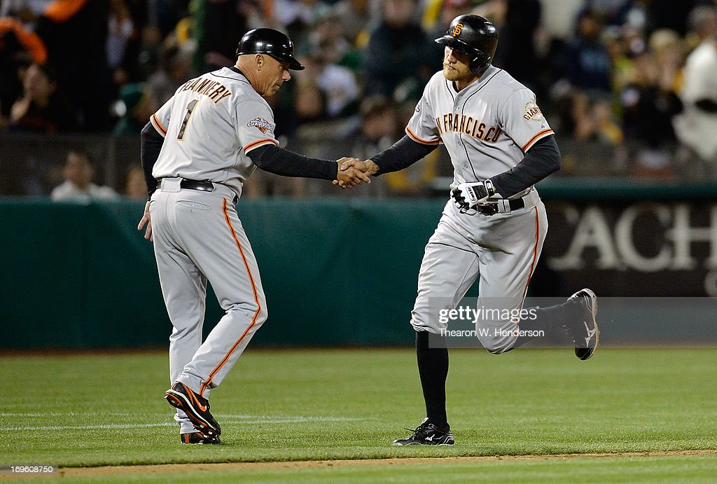 Hunter Pence #8 of the San Francisco Giants is congratulated by third base coach Tim Flannery #1 after Pence hit a solo home run against the Oakland Athletics in the ninth inning at O.co Coliseum on May 28, 2013 in Oakland, California. The Athletics won the game 6-3.