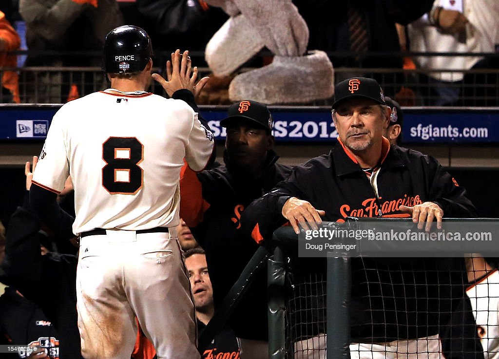 Hunter Pence #8 of the San Francisco Giants is greeted by hitting coach Hensley Meulens (C) and manager Bruce Bochy in the dugout after Pence scored in the seventh inning against the Detroit Tigers during Game Two of the Major League Baseball World Series at AT&T Park on October 25, 2012 in San Francisco, California.