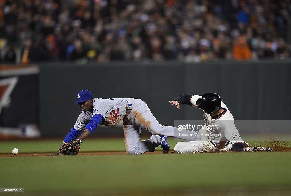 <a gi-track='captionPersonalityLinkClicked' href=/galleries/search?phrase=Hunter+Pence&family=editorial&specificpeople=757341 ng-click='$event.stopPropagation()'>Hunter Pence</a> of the San Francisco Giants is safe at second base on a throwing error from shortstop Hanley Ramirez (not pictured) to second baseman <a gi-track='captionPersonalityLinkClicked' href=/galleries/search?phrase=Dee+Gordon&family=editorial&specificpeople=7091343 ng-click='$event.stopPropagation()'>Dee Gordon</a> of the Los Angeles Dodgers in the bottom of the six inning at AT&T Park on April 15, 2014 in San Francisco, California. All uniformed team members are wearing jersey number 42 in honor of Jackie Robinson Day.