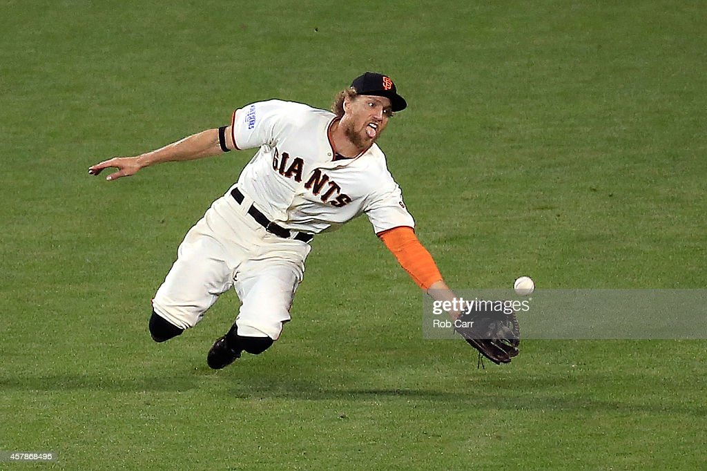 Hunter Pence #8 of the San Francisco Giants makes a diving catch on a ball hit by Lorenzo Cain #6 of the Kansas City Royals in the ninth inning during Game Four of the 2014 World Series at AT&T Park on October 25, 2014 in San Francisco, California.