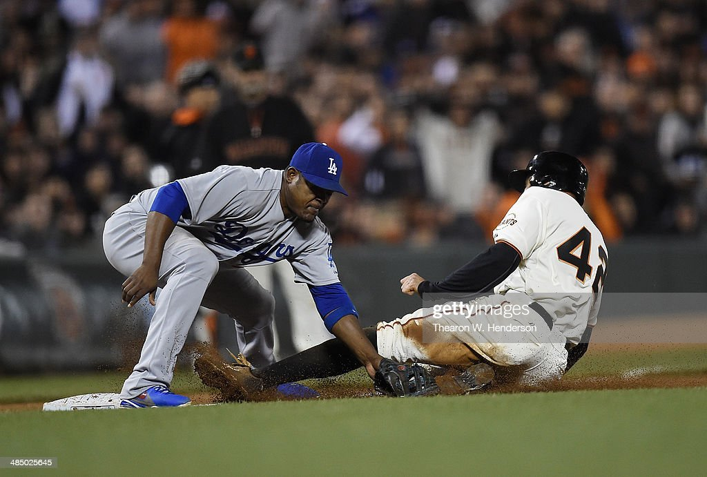 <a gi-track='captionPersonalityLinkClicked' href=/galleries/search?phrase=Hunter+Pence&family=editorial&specificpeople=757341 ng-click='$event.stopPropagation()'>Hunter Pence</a> of the San Francisco Giants makes it to third base on a wild pitch, beating the throw down to <a gi-track='captionPersonalityLinkClicked' href=/galleries/search?phrase=Juan+Uribe&family=editorial&specificpeople=209187 ng-click='$event.stopPropagation()'>Juan Uribe</a> of the Los Angeles Dodgers in the bottom of the six inning at AT&T Park on April 15, 2014 in San Francisco, California. All uniformed team members are wearing jersey number 42 in honor of Jackie Robinson Day.