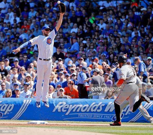 Hunter Pence of the San Francisco Giants reaches first base as Kris Bryant of the Chicago Cubs is unable to make a catch on a throwing error by Tommy...