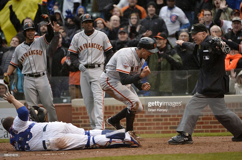 Hunter Pence #8 of the San Francisco Giants (2R) reacts after scoring past catcher Welington Castillo #53 of the Chicago Cubs on a double hit by Brandon Belt #9 of the Giants during the ninth inning at Wrigley Field on April 12, 2013 in Chicago, Illinois. Joaquin Arias #13 of the San Francisco Giants also scored on the play. The Cubs defeated the Giants 4-3.