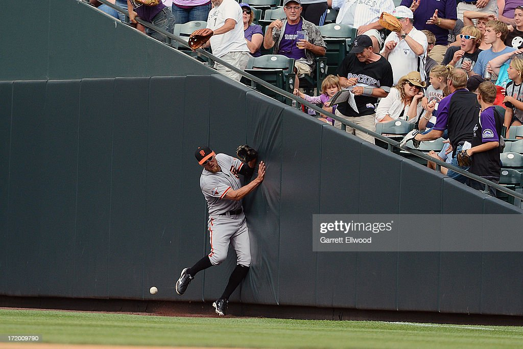 Hunter Pence #8 of the San Francisco Giants runs into the outfield wall trying to catch a fly ball during the game against the Colorado Rockies from the dug out at Coors Field on June 30, 2013 in Denver, Colorado.