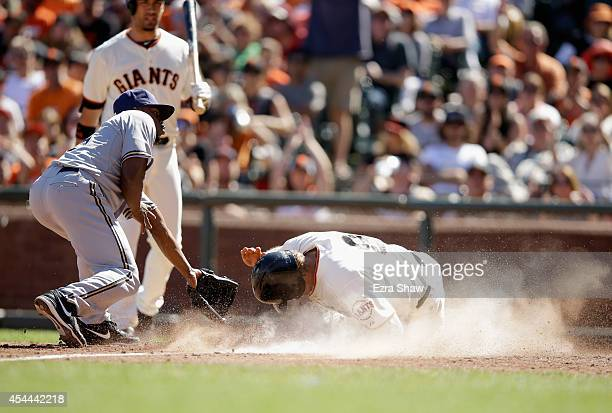 Hunter Pence of the San Francisco Giants scores on a wild pitch by Alfredo Figaro of the Milwaukee Brewers in the seventh inning at ATT Park on...