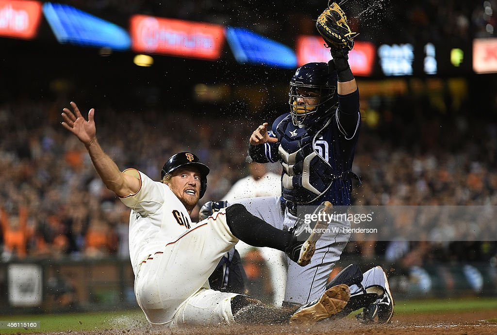 Hunter Pence #8 of the San Francisco Giants scores under the tag of Rene Rivera #44 of the San Diego Padres in the bottom of the seventh inning at AT&T Park on September 25, 2014 in San Francisco, California.