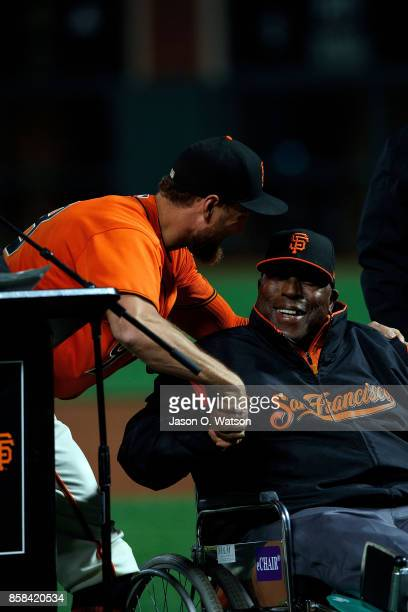 Hunter Pence of the San Francisco Giants shakes hands with Hall of Fame first baseman Willie McCovey on the field before the game against the San...