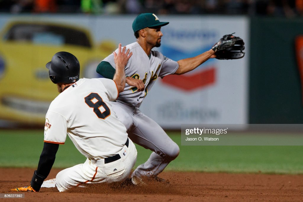 Hunter Pence #8 of the San Francisco Giants slides into second base for a double ahead of a tag from Marcus Semien #10 of the Oakland Athletics during the fifth inning at AT&T Park on August 3, 2017 in San Francisco, California. The San Francisco Giants defeated the Oakland Athletics 11-2.