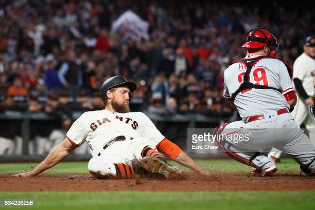 Hunter Pence of the San Francisco Giants slides past Cameron Rupp of the Philadelphia Phillies to score in the third inning at ATT Park on August 17...