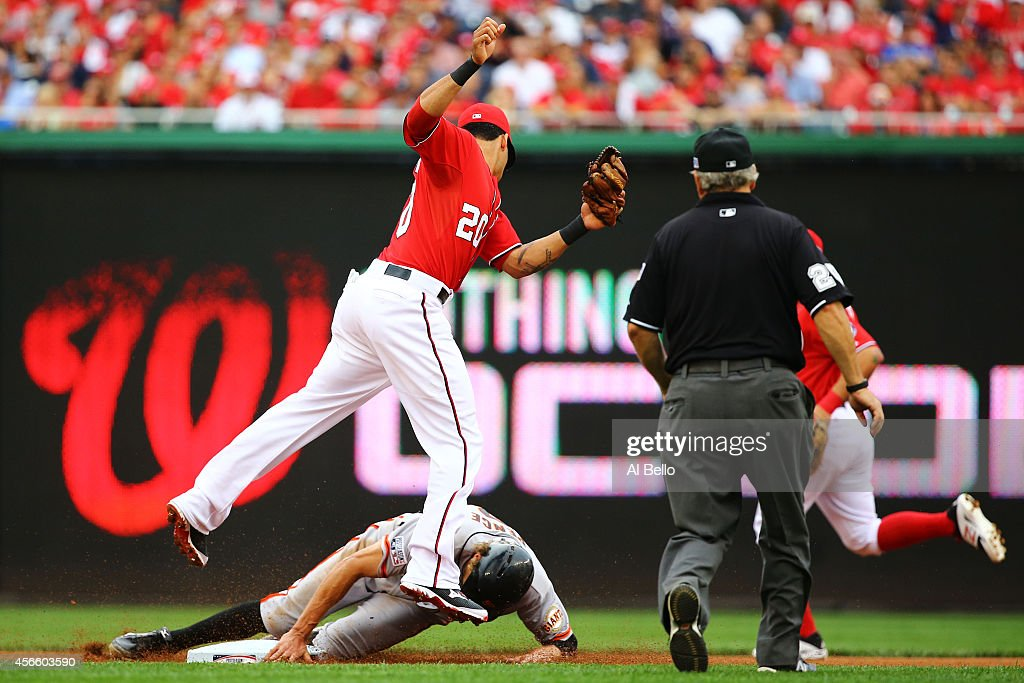 <a gi-track='captionPersonalityLinkClicked' href=/galleries/search?phrase=Hunter+Pence&family=editorial&specificpeople=757341 ng-click='$event.stopPropagation()'>Hunter Pence</a> #8 of the San Francisco Giants steals second base against <a gi-track='captionPersonalityLinkClicked' href=/galleries/search?phrase=Ian+Desmond&family=editorial&specificpeople=835572 ng-click='$event.stopPropagation()'>Ian Desmond</a> #20 of the Washington Nationals in the fourth inning during Game One of the National League Division Series at Nationals Park on October 3, 2014 in Washington, DC.